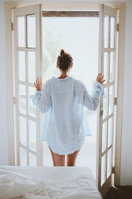 woman opening bedroom door in the morning